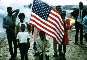 African American children with an American flag, probably during the Selma to Montgomery March. SSelma to Montgomery Rights March slide collection, Slide #2612, Alabama Dept. of Archives and History, Montgomery, Alabama.