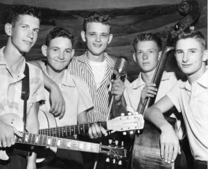 "Jerry Reed and the winners of a music contest, Atlanta, Georgia, August 8, 1956. Newspaper caption attached to print verso identifies photographer Harold Joiner: ""Winning String Band With Recording Artist Jerry Reed. L-R: Rudolph Thomas, Wendell Williams, Reed, Douglas Thomas, Gene Davis."" AJCP551-69a, Atlanta Journal-Constitution Photographic Archives. Special Collections and Archives, Georgia State University Library."