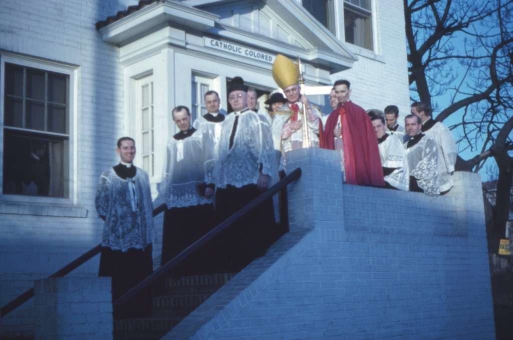 A 1941 photograph of a gathering of white Catholic clergy including several Marists on the front steps of the Our Lady of Lourdes Colored Mission (later known as the Our Lady of Lourdes Catholic Church), Atlanta's first African American Catholic church.