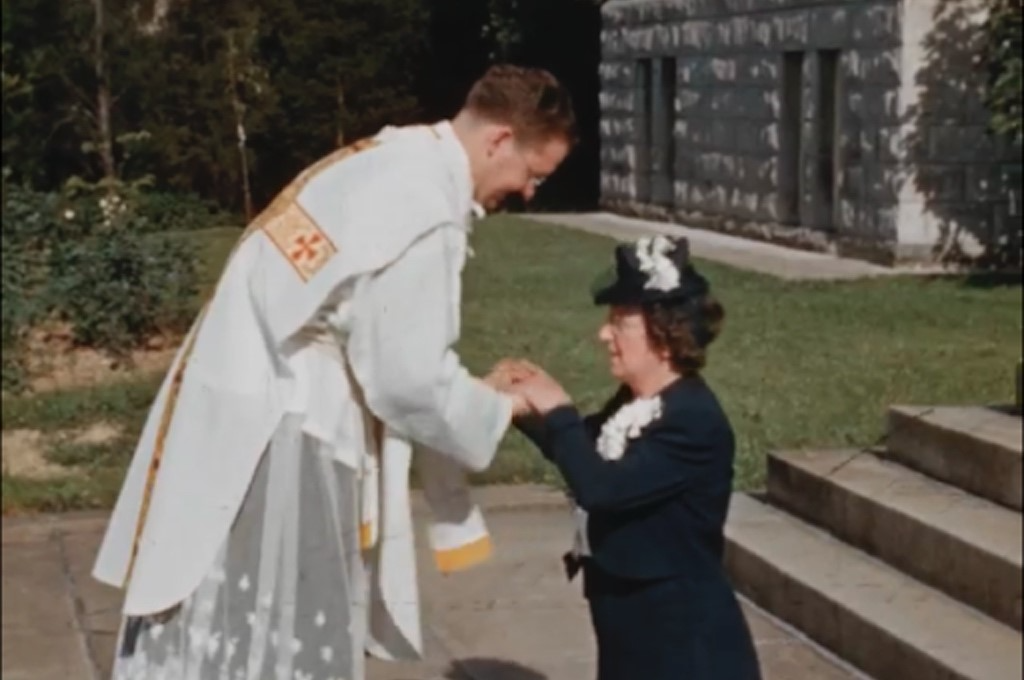 Still shot of a member of the Catholic clergy at the Marist School in Atlanta, Georgia performing rites on an elderly woman