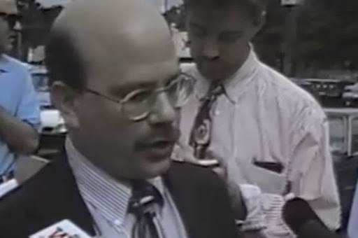 Image of LGBTQ+ activist, presenting male, speaking into a microphone during a press gaggle.