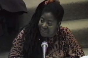 Image of civil rights activist and public intellectual Loretta Ross, seated, speaking into a microphone